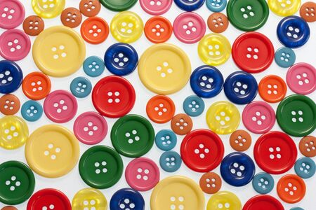 buttons sew: Lots of bright coloured buttons on white full frame view