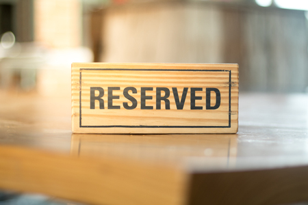 reserved sign: reserved sign made from wooden plate in restaurant Stock Photo