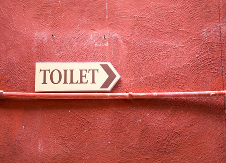 signage: toilet plate signage on red wall texture