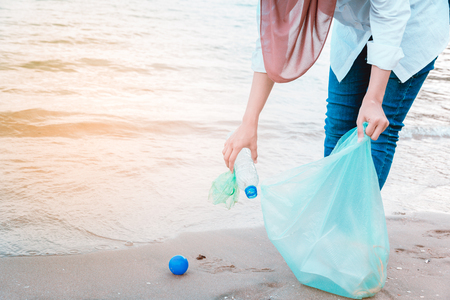 Women's hand picking up trash by the beach.