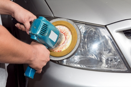 Car headlights with power buffer machine at service station. photo
