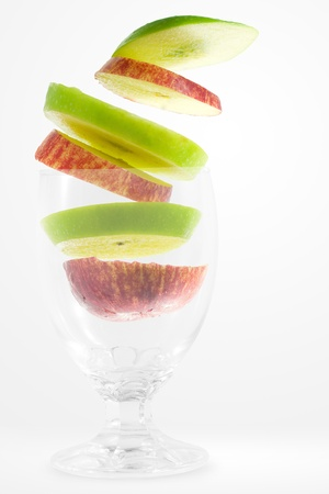 Slices of red and green apple falling into a glass  photo