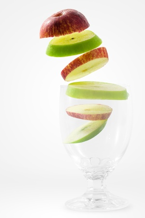 slash: Slices of red and green apple falling into a glass  Stock Photo