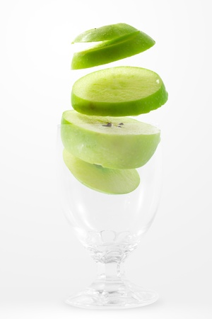 Slices of green apple falling into a glass  photo