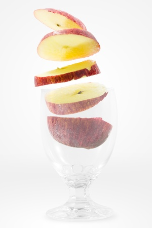 Slices of red apple falling into a glass photo