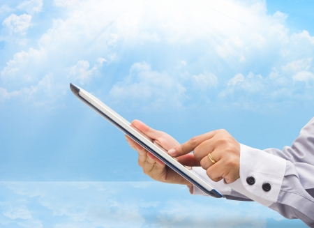 hands are holding and point on touch screen device  on blue sky cloud computing concept  photo