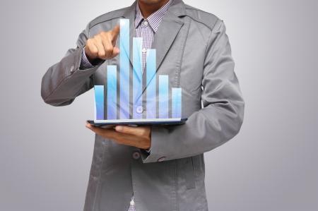 crisis economica: Los hombres de negocios, mano que se�ala en el gr�fico de la pantalla t�ctil en una tableta