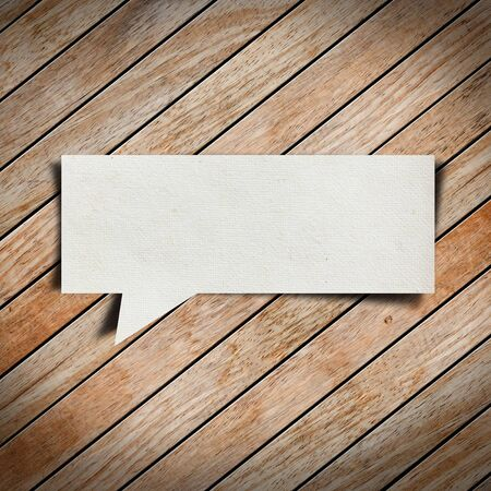 Paper speech bubble on wood background photo