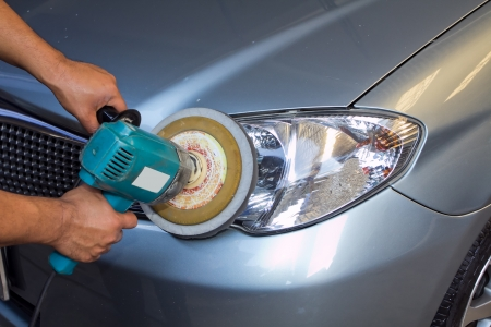 car polish: Car headlights with power buffer machine at service station - a series of CAR CARE images