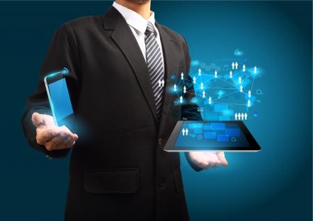 ic�ne logiciel: La technologie sans fil moderne et le concept des m�dias sociaux, t�l�phone mobile avec un ordinateur tablette dans la main