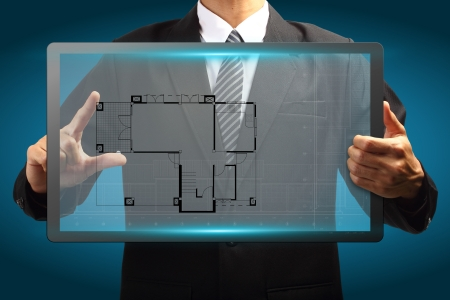 architecture plans: Touch screen interface House blueprints in the hands of businessmen