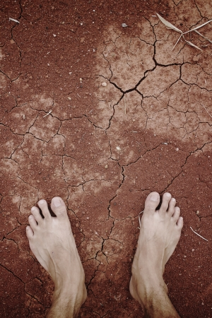 Barefoot standing on dry and cracked earth background photo