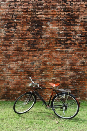 Vintage bicycle and red brick wall, vintage bike  Retro stylish cycling in town photo