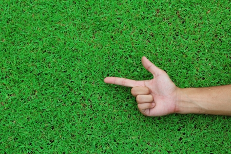 Human hand point with finger on green grass background texture photo