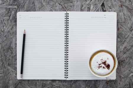 Cup of coffee and notebook paper on a wooden table photo