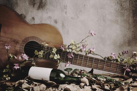 Stilleven wijnfles met akoestische gitaar Stockfoto