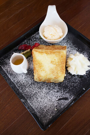 Toast with honey and ice cream in plate on table photo