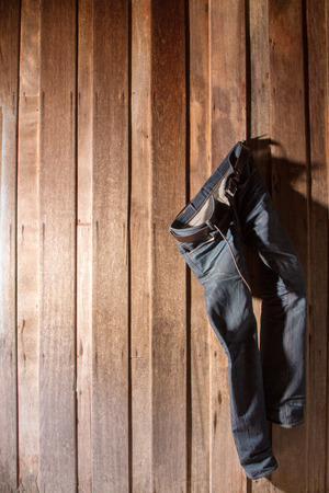 Jeans hanging wooden wall photo