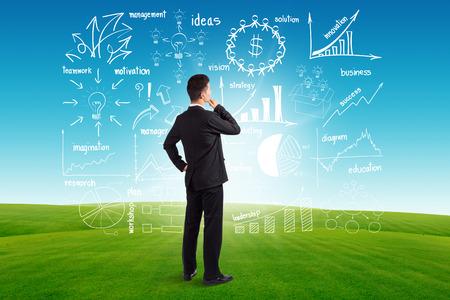 pensador: Empresario busca a los futuros gráficos de dibujo creativos y gráficos éxito empresarial idea plan estratégico, en el cielo azul y la hierba verde de fondo Foto de archivo