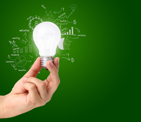 Hand holding light bulb with drawing charts and graphs business success strategy plan idea, Inspiration concept modern design photo