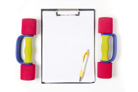Blank notepad paper and pen and dumbbell, isolated on white background photo