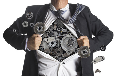 Businessman showing a superhero suit underneath machinery metal gears idea concept, isolated on white background photo