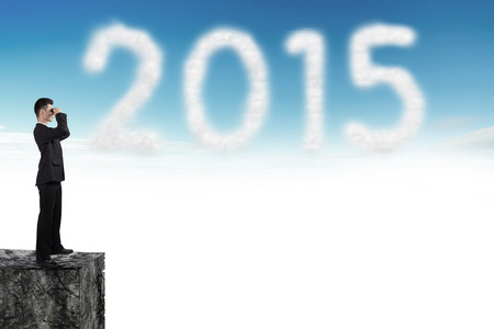 business man looks through a telescope on cloud in blue sky with a shaped of number 2015 photo