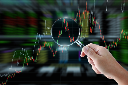 Hand holding magnifying glass with stock market graph background