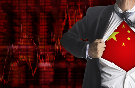 financial graph: Stock market chart background with china flag with businessman showing a superhero suit underneath his suit