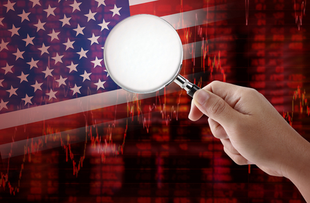 shareholding: Crisis in USA - Shares Fall Graph on United States of America Flag with hand holding magnifying glass analyze solution ideas concept design