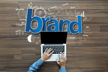 Markenidentität Ideen Konzept, Kreatives Denken Zeichnung Diagramme und Grafiken Strategieplan auf Holztisch Hintergrund, Inspiration Konzept mit Geschäftsmann auf Laptop-Computer PC, Top View