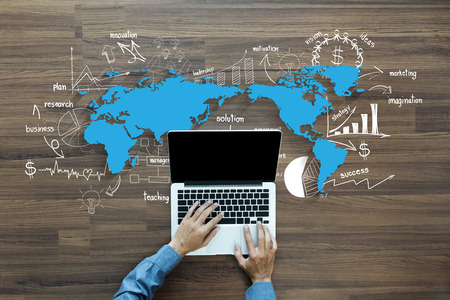 Weltkarte mit kreativen Zeichnung Diagramme und Grafiken Geschäftserfolg Strategieplan Ideen, mit Mann Hand auf Laptop-Computer-Tastatur mit leeren Bildschirm Monitor, Ansicht von oben