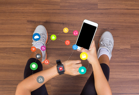 application software: Fitness woman hand with application icons wearing watchband touchscreen smartwatch with holding mobile phone, View from above studio shot on wooden floor background Stock Photo