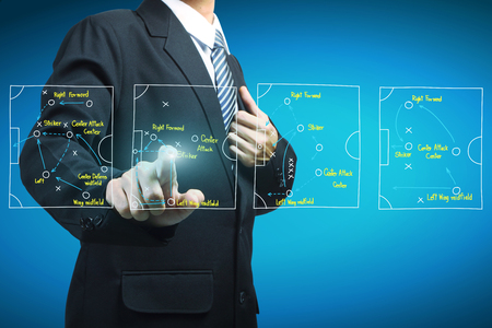 Plan of soccer manager pointing to strategy tactical board Standard-Bild