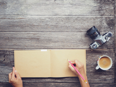 book concept: Working table with notebook paper, coffee cup , Pencil, Vintage camera , Wooden desk background with copy space on top. Soft focus with noise. Instant photo vintage split toning color effect. Stock Photo