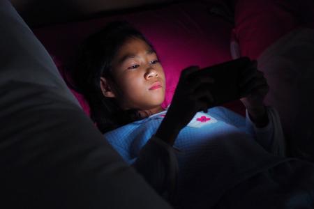 sleeping tablets: Girl using mobile phone on dark bed in the bedroom