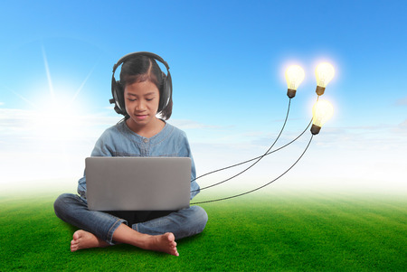 plugged in: Little girl using a laptop with creative light bulb ideas plugged in it, Sitting on green grass field clouds blue sky nature landscape