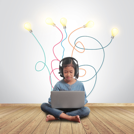 plugged in: Little girl using a laptop with creative light bulb ideas plugged in it, Sitting on wall room with a hardwood wooden floor