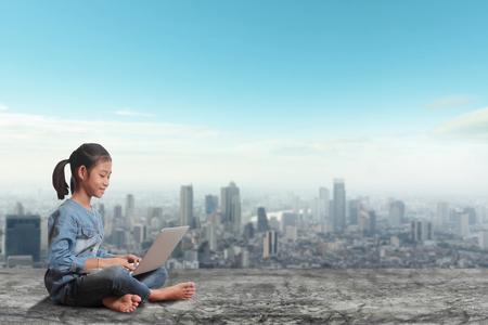 Little girl sitting using laptop computer on modern city skyline, city street, cityscape, landscape, building with skyline and background Stock Photo