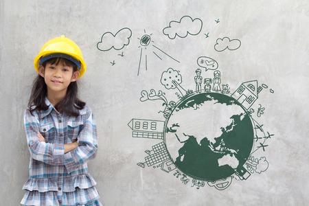 Petit génie de fille avec le dessin créatif sur la carte du monde environnement avec famille heureuse, eco amical, économiser de l'énergie, contre un mur de briques