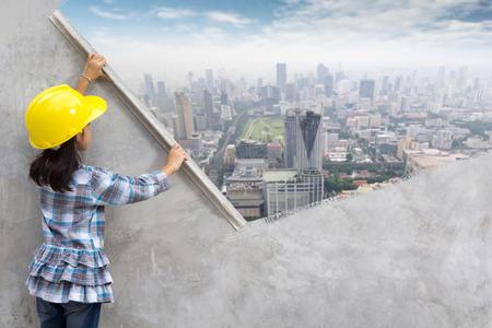 손 집을 리모델링 석고 도구를 들고 어린 소녀 엔지니어링 아이디어 개념. 벽에 그림 현대 도시의 스카이 라인, 도시 거리, 도시 풍경, 풍경, 빌딩, 초고