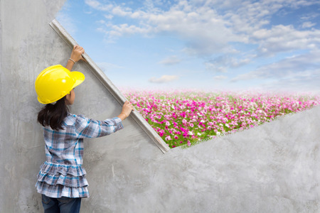Little girl engineering ideas concept with hand holding plastering tools renovating a house. With painting flowers grass field blue sky clouds nature landscape on wall