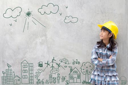 Little Girl Engineering mit kreativen Zeichnung Umwelt mit glücklicher Familie, umweltfreundlich, sparen Energie, gegen eine Mauer