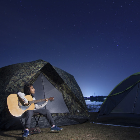glows: Girl playing guitar at tent glows under a night sky stars