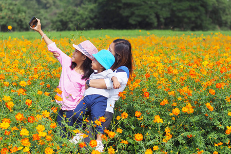 Mother and daughter taking photo with phone selfie in flower garden 스톡 콘텐츠