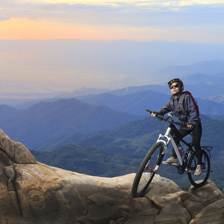 steep: Female biker riding on bicycle in mountains on sunset