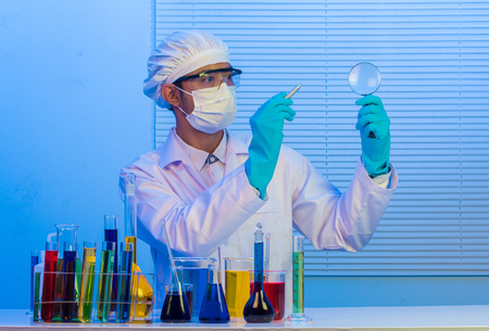 Man scientist holding pen with magnifying glass Stock Photo