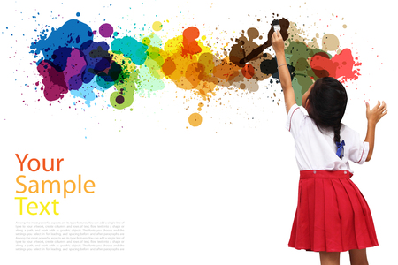 girl holding a paint brush painting on a white wall Stock Photo