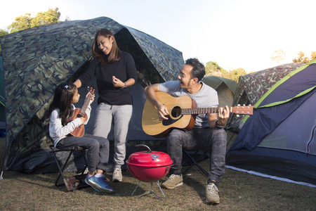 Happy family on a camping trip, Parents and daughters are singing guitar.
