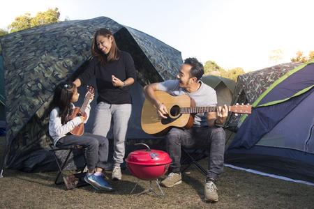 Gelukkige familie op een camping trip, Ouders en dochters zingen gitaar.